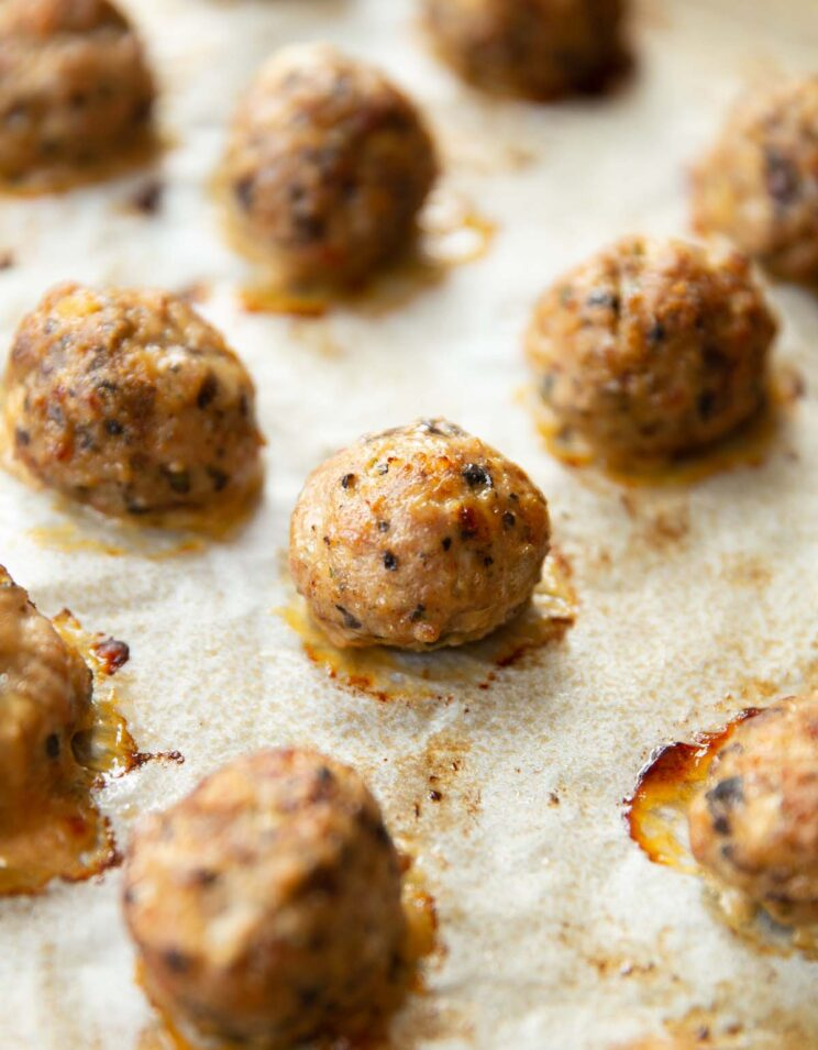 close up shot of meatballs fresh out the oven on large baking tray
