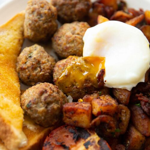 breakfast meatballs on white plate served with poached egg, toast tomato and potatoes