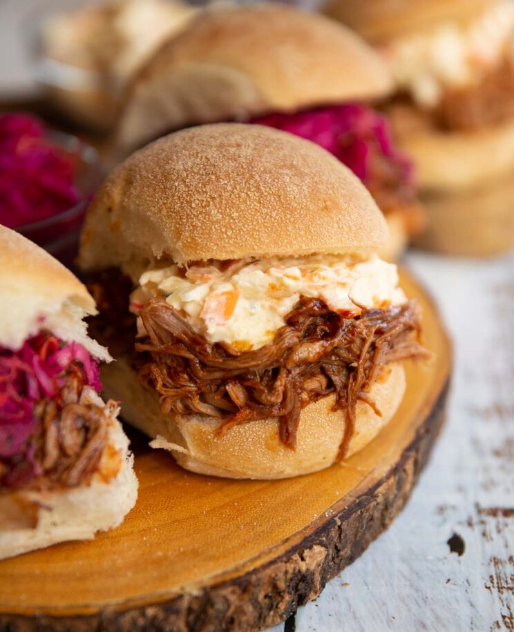 close up shot of pulled pork sandwich on wooden board