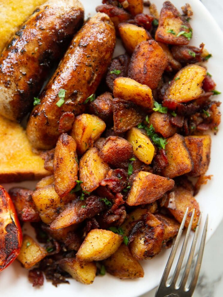 overhead shot of breakfast potatoes on white plate served with sausages, tomato and toast