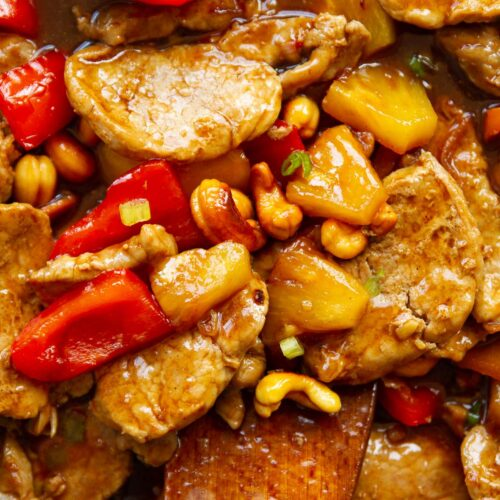 close up overhead shot of pork and pineapple with wooden spoon digging in
