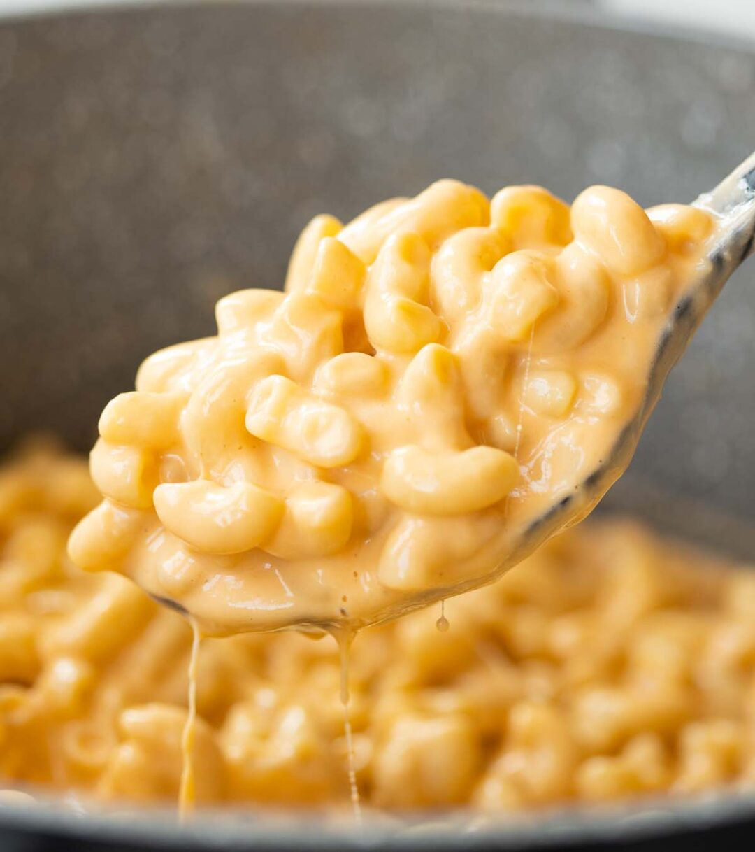 close up shot of mac and cheese on serving spoon scooping out of pot