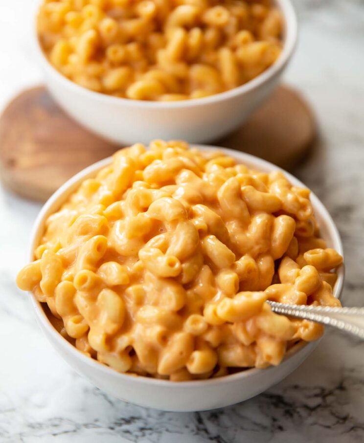 two small white bowls of mac and cheese on marble backdrop