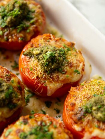 stuffed tomatoes in large white baking dish fresh out the oven with dollop of pesto