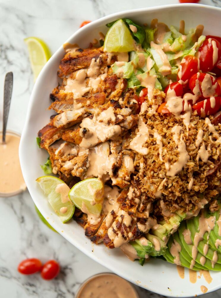 overhead close up shot of half of grilled chicken salad in large white bowl