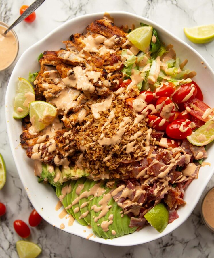 overhead shot of grilled chicken salad in large white serving bowl on marble background